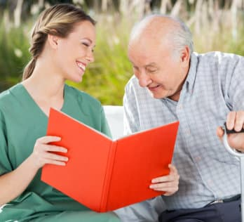 caregiver letting senior man read a book