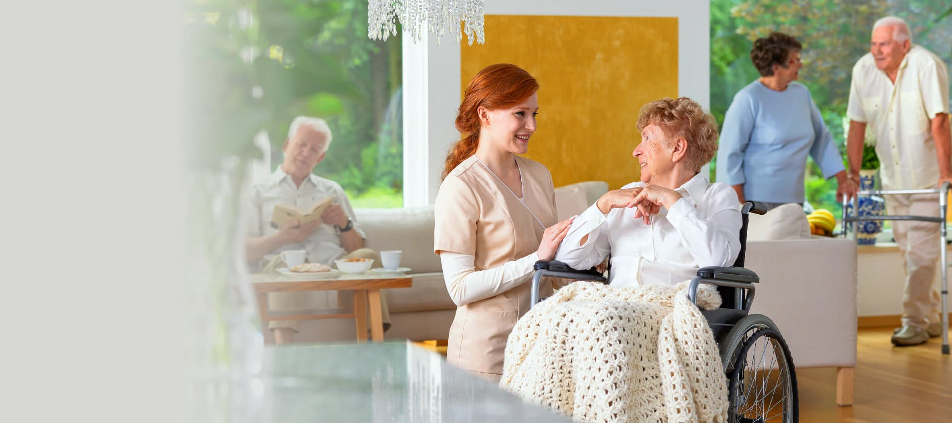 caregiver talking to a senior woman with seniors on their background
