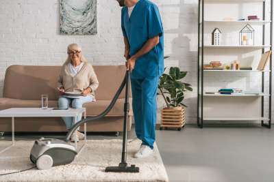 cropped shot of social worker cleaning carpet with vacuum cleaner while senior woman reading newspaper