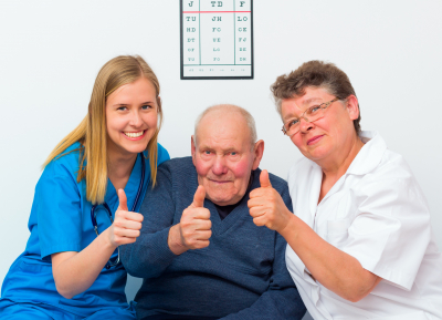 happy moments at the nursing home, elderly man showing thumbs up with his caregivers