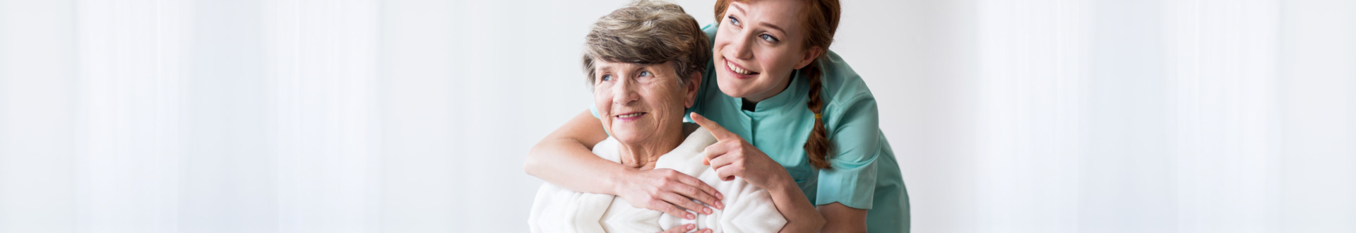caregiver pointing at something while senior woman looking